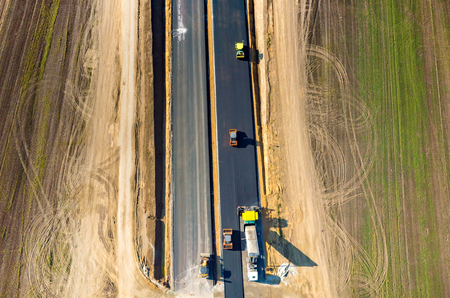 heavy equipment operator: Aerial view on the new asphalt road under construction