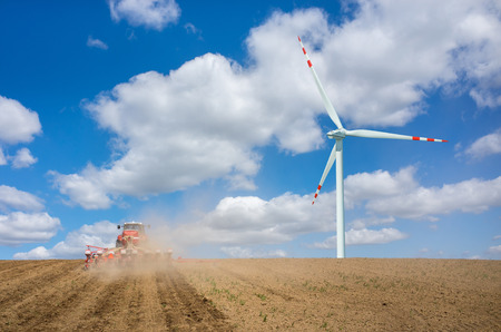 harrowing: Aerial view on the windmill and the tractor harrowing the large brown field in spring season Stock Photo