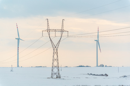 powerlines: Large view on the windmill and powerlines on the field in winter season Stock Photo