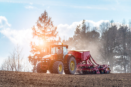 harrowing: Beatiful sunset above the tractor harrowing the field in spring season Stock Photo