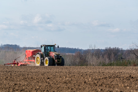 plough land: Large view on the tractor harrowing the field in spring season