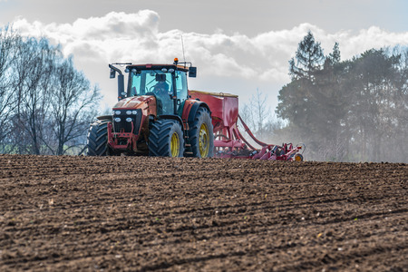 harrowing: Large view on the tractor harrowing the field in spring season