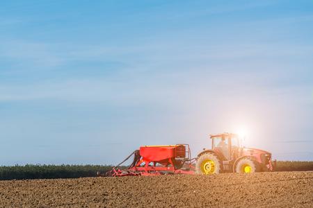 harrowing: Beatiful sunset above the tractor harrowing the field in spring season Stock Photo