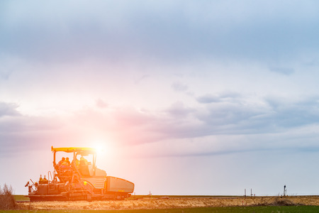 blacktopping: Sunset above the road roller building the new asphalt road Stock Photo