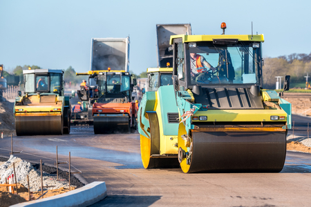 compacting: Large view on the road rollers working on the new road construction site Stock Photo