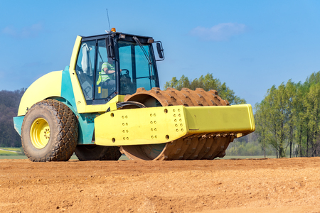 vibroroller: Large view on the compactor working on the new road construction site Stock Photo