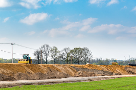 vibroroller: Large view on the compactors working on the new road construction site Stock Photo