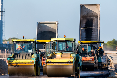 blacktopping: Large view on the road rollers working on the new road construction site Stock Photo