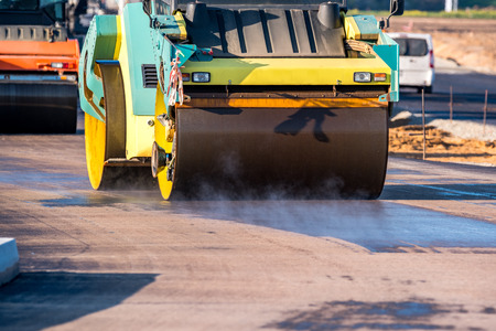 macadam: Large view on the road rollers working on the new road construction site Stock Photo