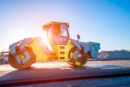 Beautiful sunset above the road roller working on the new road construction site Reklamní fotografie