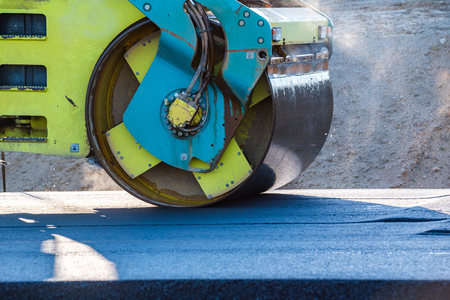 blacktopping: Close view on the road roller working on the new road construction site
