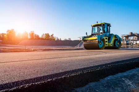 ロード ローラーが新しい道路建設現場での作業上の美しい夕日 写真素材
