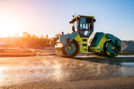 macadam: Beautiful sunset above the road roller working on the new road construction site Stock Photo