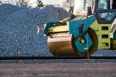 compacting: Close view on the road roller working on the new road construction site
