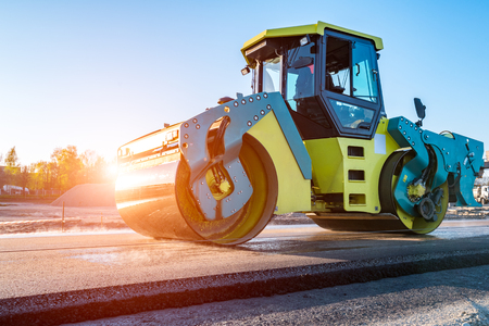 steam roller: Beautiful sunset above the road roller working on the new road construction site Stock Photo
