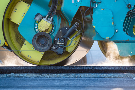 vibroroller: Close view on the road roller working on the new road construction site