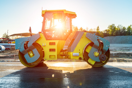 construction vibroroller: Beautiful sunset above the road roller working on the new road construction site Stock Photo