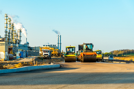 vibroroller: Large view on the road rollers working on the new road construction site Editorial