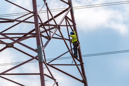 Large view on the worker climbing on the high dangerous powerlines