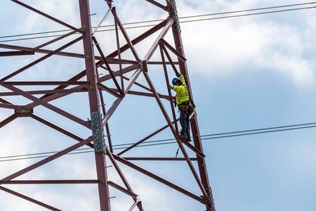 Groot zicht op de werker die beklimt op de hoge gevaarlijke krachtlijnen Stockfoto