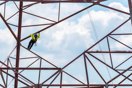 Groot zicht op de werker die op de gevaarlijke hoogspanningskabels klimt