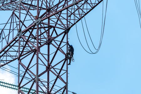 heights job: Large view on the worker climbing on the high dangerous powerlines