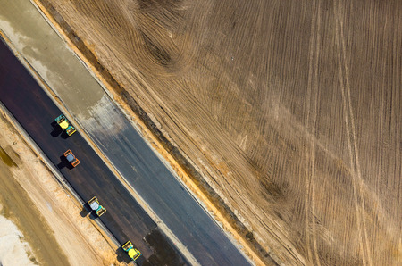 compacting: Aerial view on the road rollers working on the new road construction site