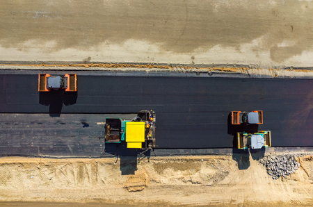 steam roller: Aerial view on the road rollers working on the new road construction site