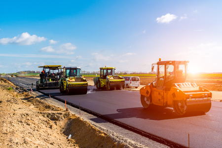 vibroroller: Beautiful sunset above the road roller working on the new road construction site Stock Photo