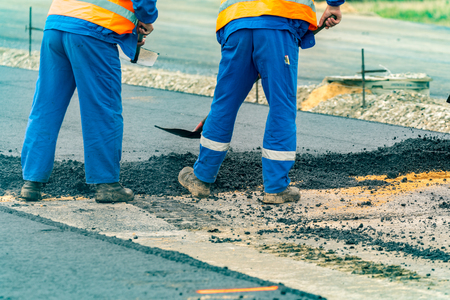 asphalting: Close view on the workers and the asphalting machines