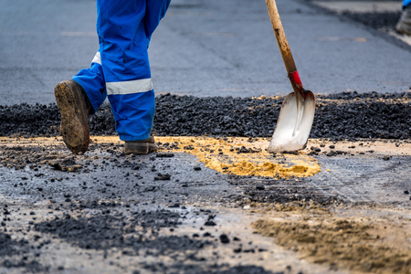 asphalting: Close view on the worker and the asphalting machines Stock Photo