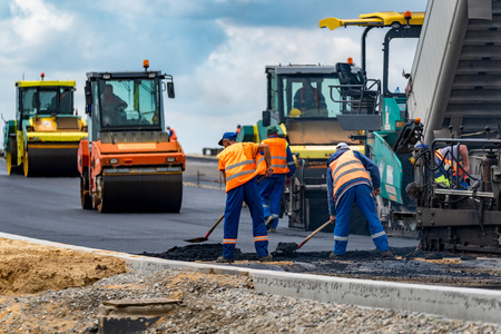 blacktop: Close view on the workers and the asphalting machines