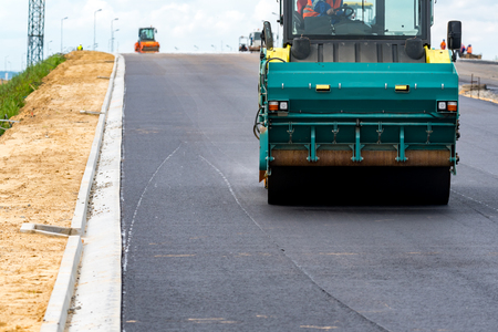 compaction: Close view on the road rollers working on the new road construction site Stock Photo