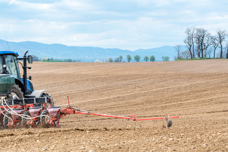harrowing: Close view on the tractor harrowing the field in spring season