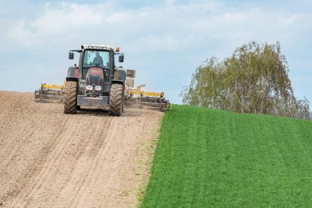 Duży widok na ciągnik broniący pola w sezonie wiosennym Zdjęcie Seryjne - 69782000