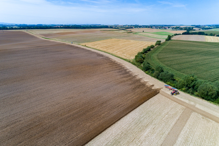 Aerial view on the tractor harrownig the large brown field Stok Fotoğraf