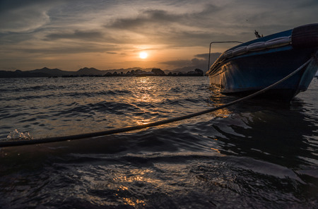 dignified: sunset with the boat at sea