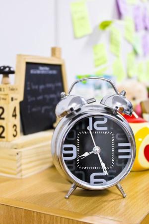 Black and metallic alarm clock in room photo