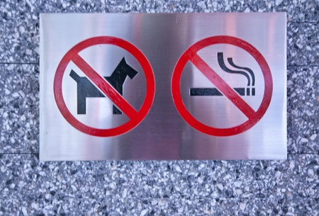 poorly: some metallic prohibited signs on the stones wall - Prohibited dog and smoking