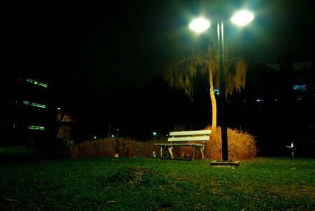 Night view with old fashioned street light and bench under the warm lantern and tree in the night park