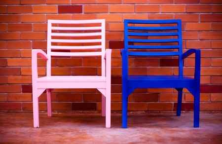 pink and blue chairs with brick wall background - couple chairs photo