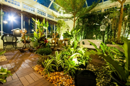 Beautiful garden with white beauty bench and rocking horse chairs in night scene