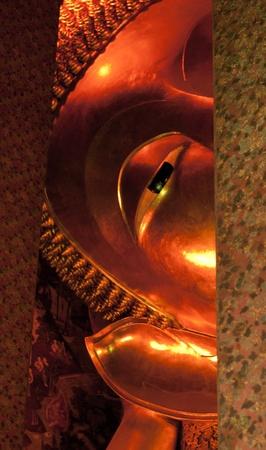 Golden Reclining Buddha - Face of Golden Reclining Buddha in Thailand,Wat Pho, Bangkok photo