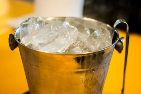 closeup ice in a bucket - ice in pail with tong on the yellow table Stock Photo - 13803063