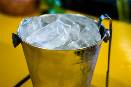 ice in a bucket - ice in pail with tong on the yellow table Stock Photo - 13803043