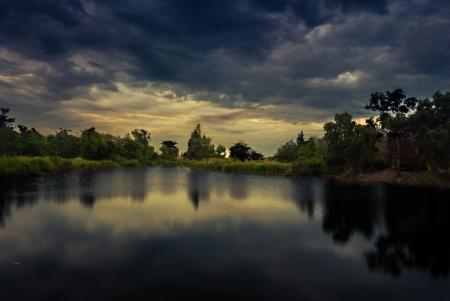 Rain clouds and gloomy sky in black with some sunshine through out the dark cloud Stock Photo - 13803072