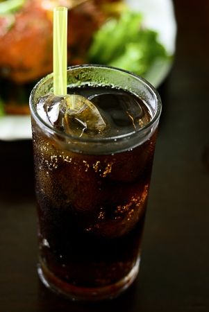 Cola into a glass with ice cubes - Cola glass with food background - glass of cola with ice and straw - Fresh Cold Cola with ice in glass