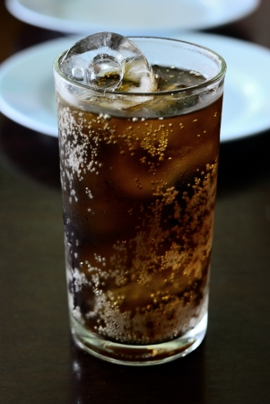 Cola into a glass with ice cubes - Cola glass with food background - glass of cola with ice - Fresh Cold Cola with ice in glass