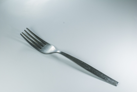 silver spoon and fork in shallow focus close up - isolated on white background photo
