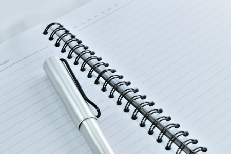 Blank notebook with date and day - White paper texture background - Ballpoint pen on checked notebook paper photo